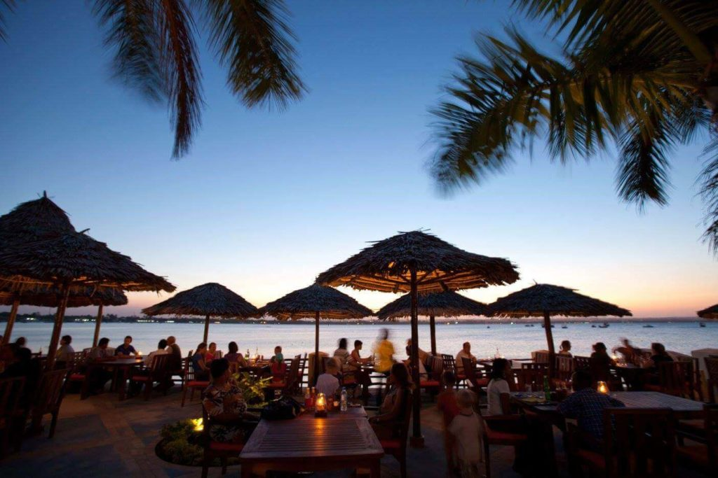 This image has an empty alt attribute; its file name is tanzania_safari_holidays_waterfront_sunset_restaurant-1024x683.jpg